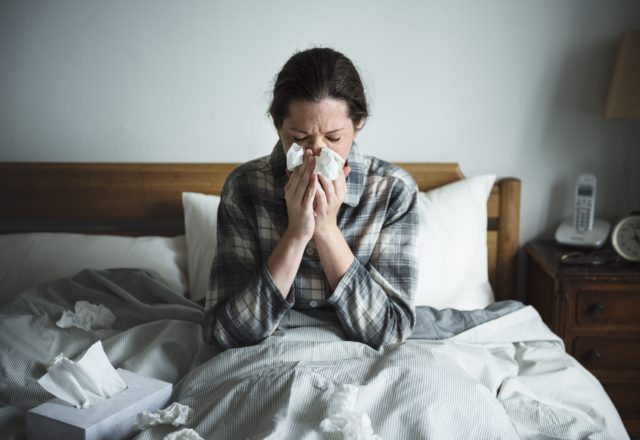 A woman sick in bed without a flu vaccination