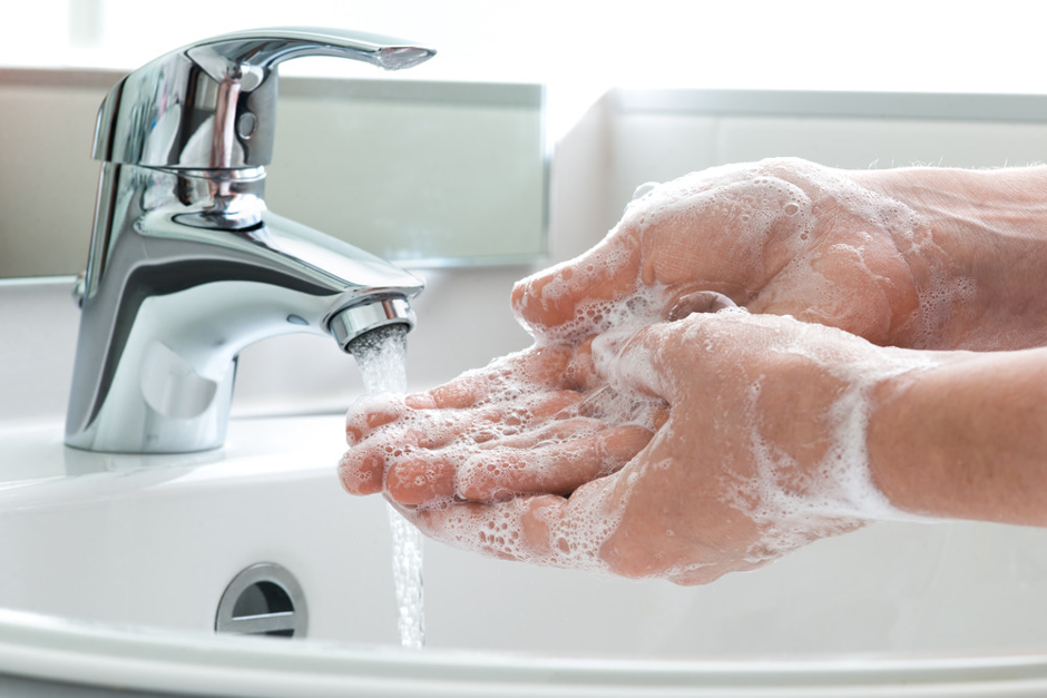 person washing hands to remove germs
